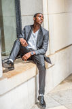 Young African American Man thinking outside in New York. Young African American man wearing black fashionable jacket, white undershirt, black pants, leather Stock Photography