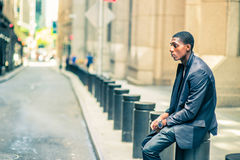 Young African American Man thinking outside on street in New Yor. Man thinking outside. Young black teenage boy is sitting on street, hunchbacked, sad, tired Stock Image