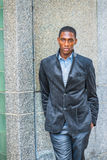Young African American Man thinking outside on street in New Yor. Young African American Man wearing new style black blazer, two hands putting in pockets Royalty Free Stock Images