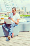 Young African American Man traveling, working on laptop computer Stock Photos