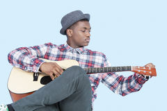 Young African American man tuning guitar over light blue background Royalty Free Stock Photography