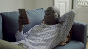 Young African American man using smartphone on couch