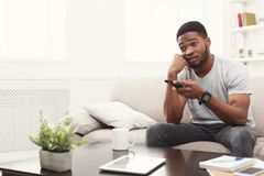 Young man watching tv at home. Young african-american man watching tv. Emotional guy pointing with remote controller on tv-set. Man worrying about favourite Royalty Free Stock Photography