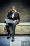 Young African American Man working on laptop computer outside in. Young African American Man wearing black blazer, pants, leather shoes, sitting on marble stone Stock Photos
