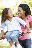 Young African American Mother And Daughter Cycling In Park Royalty Free Stock Images