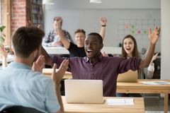 Young african american office worker celebrating achievement at. Young african american office worker throws hands in air celebrating achievement at work royalty free stock photos