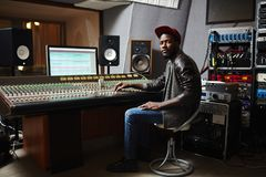Young musician. Young African-american rapper in baseball cap, jeans and leather jacket working by switchboard in studio Royalty Free Stock Images
