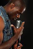 Young African American Singer with microphone. Young African American Singer with vintage microphone isolated on a dark background Royalty Free Stock Photo