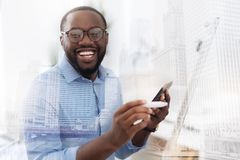 Young African American smiling at you. Feeling happy. Close up of young African American with glasses looking at you while holding a mobile phone in the hand Royalty Free Stock Photo