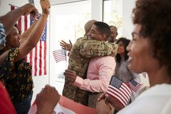 Young African American  soldier returning home to a surprise family party, selective focus. Young black soldier returning home to a surprise family party stock image