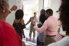 Young African American  soldier returning home to a surprise family party, selective focus, over shoulder view. Young black soldier returning home to a surprise royalty free stock photos