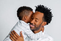 Young African American Son Hugs His Father. A young African American son hugs his father around the neck.  They are both dressed in white against a white Stock Photo