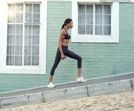 Young african american sports woman stretching legs Stock Photos