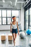 young african american sportswoman in headband and wristbands exercising on step platform stock photography