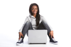 Young african american student girl with computer. Beautiful black student girl sitting on floor with a laptop computer between her legs. She is dressed casually royalty free stock photos