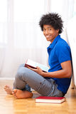 Young african american student reading books - African people. Young african american student seated on the floor reading books - African people Stock Photography