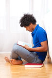 Young african american student reading books - African people. Young african american student seated on the floor reading books - African people Stock Photos