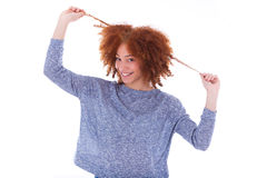 Young african american teenage girl holding her curly hair isol. Ated on white background stock image