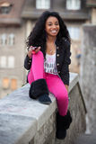 Young african american teenage girl listenin. Outdoor of a portrait happy young african american teenage girl listening to music royalty free stock image