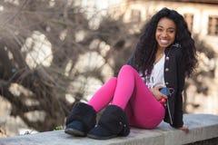 Young african american teenage girl listenin Stock Photos