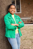 Young African American teenage girl standing outside and smiling. Royalty Free Stock Photo