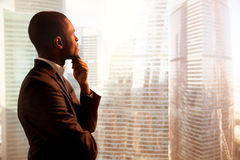 Young african-american thoughtful businessman looking through wi royalty free stock photography