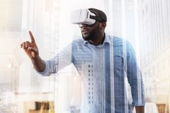 Young African American wearing virtual glasses. Real magic. Waist up of young African American wearing virtual glasses and being concentrated while putting his Royalty Free Stock Image