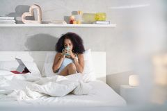 Woman Drinking Coffee Watching Movie In Bed on Sunday. Young African American woman in bed at home during weekend. Happy black girl smiling while watching movie Stock Image