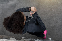 Young African American woman checks activity tracker. During outdoor exercise Stock Images