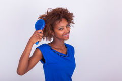 Young African American woman combing her frizzy afro hair - Black people royalty free stock image