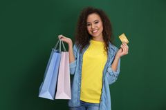 Young African-American woman with credit card and shopping bags on color background royalty free stock photo