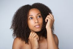 Young african american woman with curly afro hair. Close up portrait of a beautiful young african american woman with curly afro hair Royalty Free Stock Images