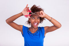 Young African American woman cutting her frizzy afro hair with s. Cissors - Black people stock image