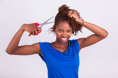 Young African American woman cutting her frizzy afro hair with s. Cissors - Black people royalty free stock photo
