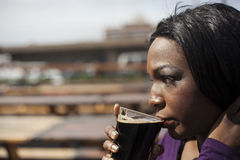 Young African American WomanDrinks a Stout Stock Image