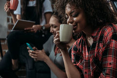 Young african american woman drinking coffee while friends using smartphone and holding cup behind. Happy young african american women drinking coffee while Stock Photo