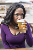 Young African American Woman Drinks Pint of Pale Ale Stock Photos
