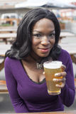 Young African American Woman Drinks Pint of Pale Ale Royalty Free Stock Image