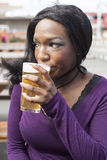 Young African American Woman Drinks Pint of Pale Ale. Young African American woman drinks a pale ale from a pint glass Royalty Free Stock Photography