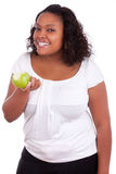 Young african american woman eating an apple. Young african american woman eating an  green apple, isolated on white background Stock Photos
