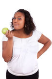 Young african american woman eating an apple. Young african american woman eating an  green apple, isolated on white background Royalty Free Stock Image