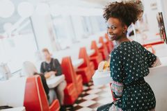 Young african american woman eating in the diner Royalty Free Stock Photo
