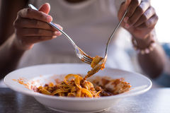 A young African American woman eating pasta royalty free stock photos