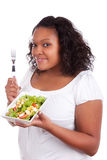 Young african american woman eating salad. Isolated on white background Stock Image