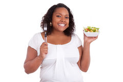 Young african american woman eating salad. Isolated on white background Stock Images