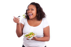 Young african american woman eating salad. Isolated on white background Royalty Free Stock Photography
