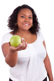 Young african american woman giving an green apple. Young african american woman giving an  green apple, isolated on white background Stock Images