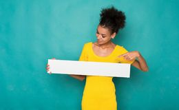 Young african-american woman holding blank banner. Young african-american woman holding blank white banner with copy space on blue background Royalty Free Stock Photo