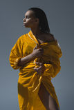 Young african american woman holding yellow raincoat and looking away. Gorgeous young african american woman holding yellow raincoat and looking away Stock Images