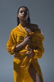 Young african american woman holding yellow raincoat and looking at camera. Gorgeous young african american woman holding yellow raincoat and looking at camera Stock Photo